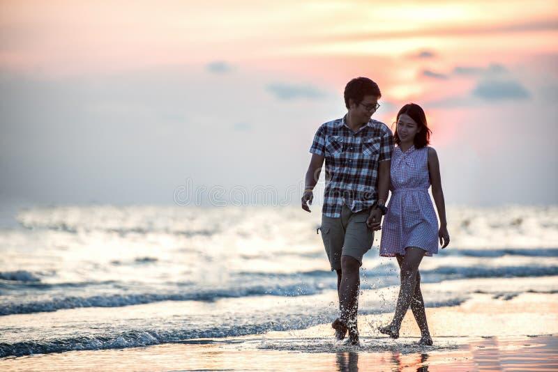 Paare, die auf Strand bei Sonnenuntergang schlendern