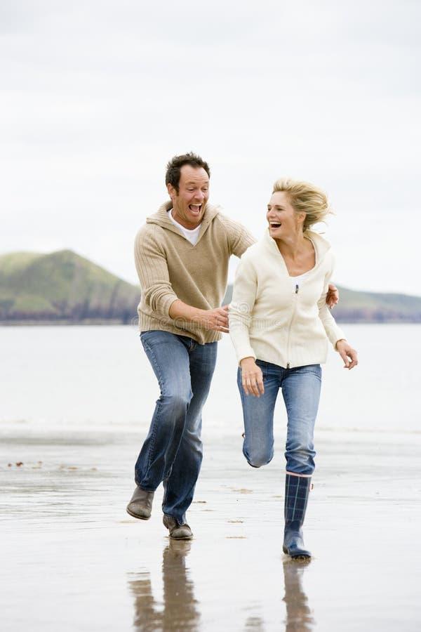 Paare, die auf Strand laufen lizenzfreie stockfotografie