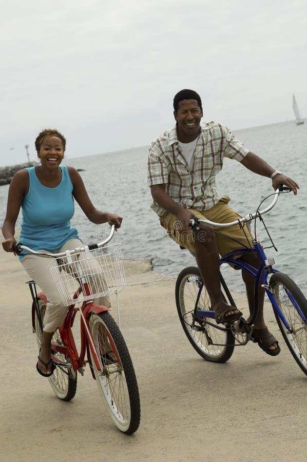 Paare, die auf Strand radfahren stockfotografie