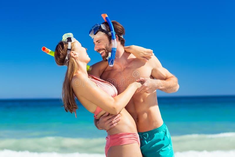 Paare, die auf Strand sich umfassen lizenzfreies stockbild