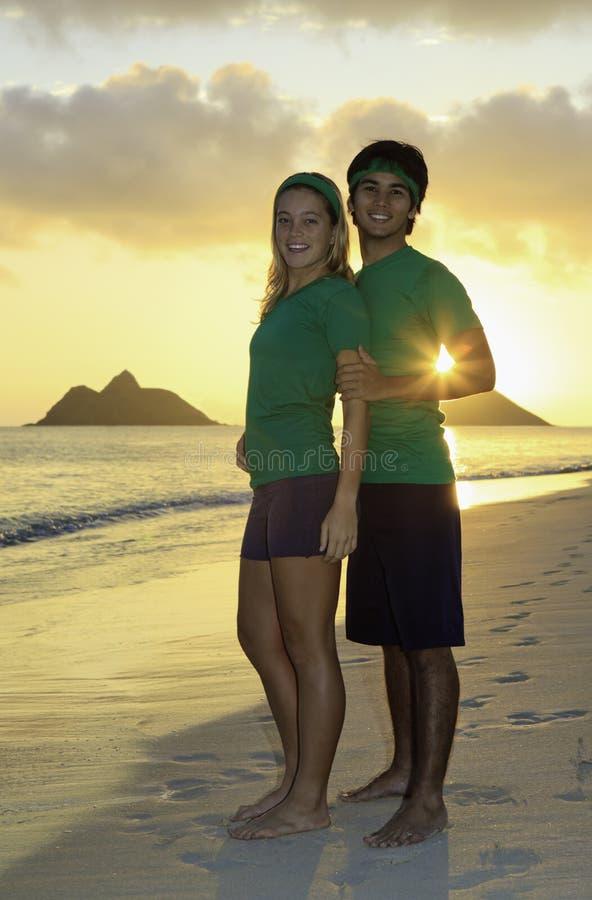 Paare, die auf Strand am Sonnenaufgang trainieren lizenzfreies stockfoto