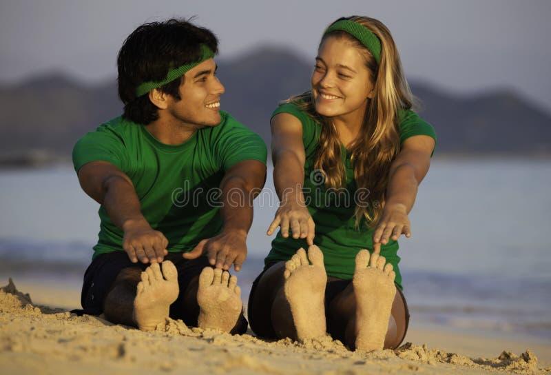 Paare, die auf Strand am Sonnenaufgang trainieren stockbild