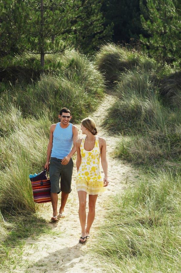 Paare, die auf Strand-Spur gehen stockfotos