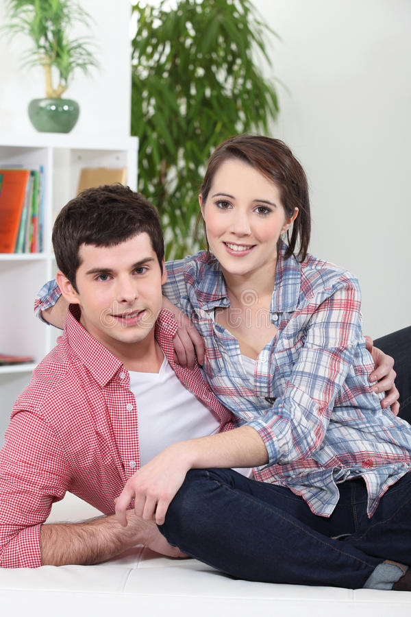 Paare, die auf weißem Sofa umarmen stockfoto
