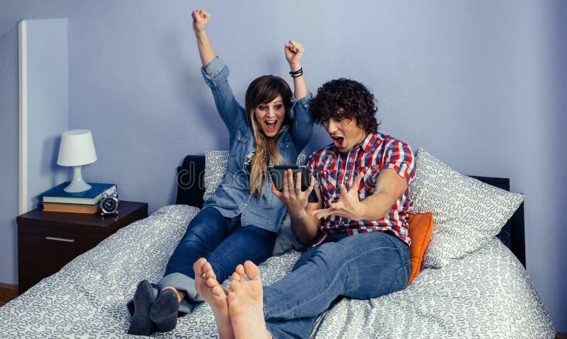 Paare, die aufpassenden Sport des Sieges feiern lizenzfreie stockfotografie