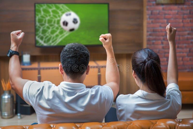 Paare, die aufpassendes Fußballspiel des Spaßes haben lizenzfreie stockfotos