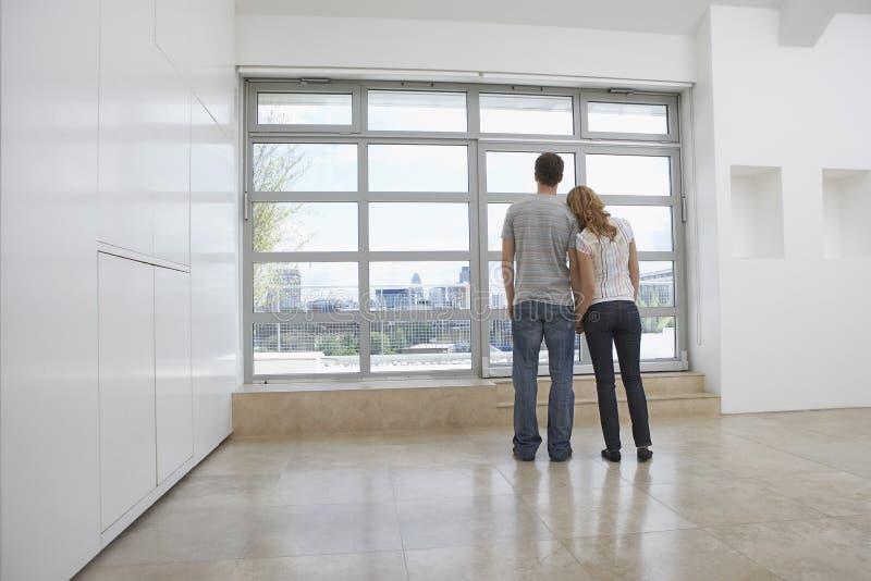 Paare, die aus Fenster in der leeren Wohnung heraus schauen lizenzfreie stockbilder