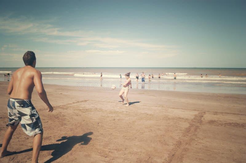Paare, die Ball in einem Strand spielen lizenzfreie stockfotos