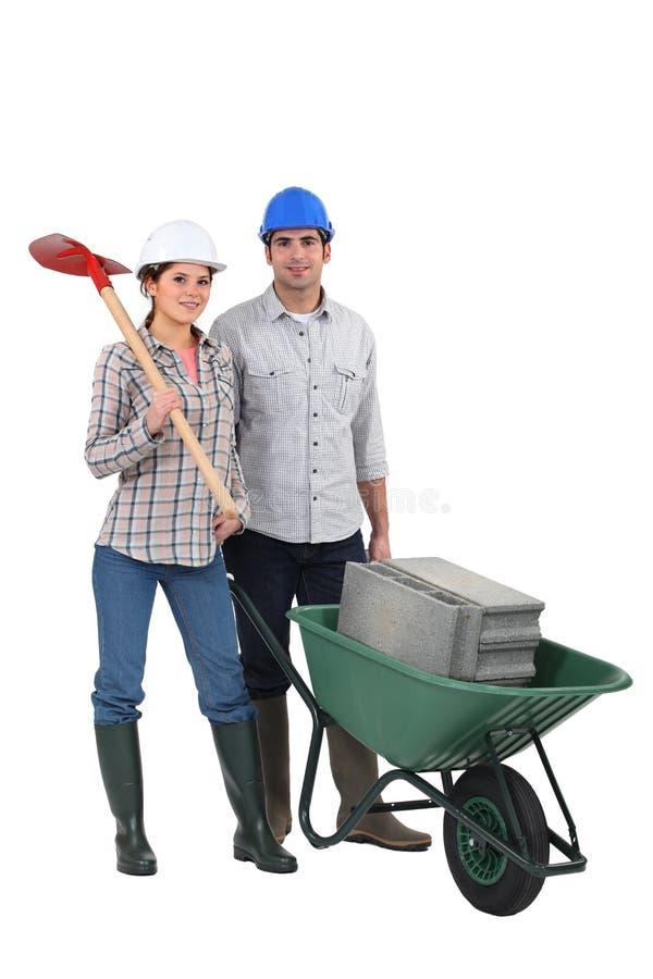 Paare, die Bausteine transportieren stockbilder