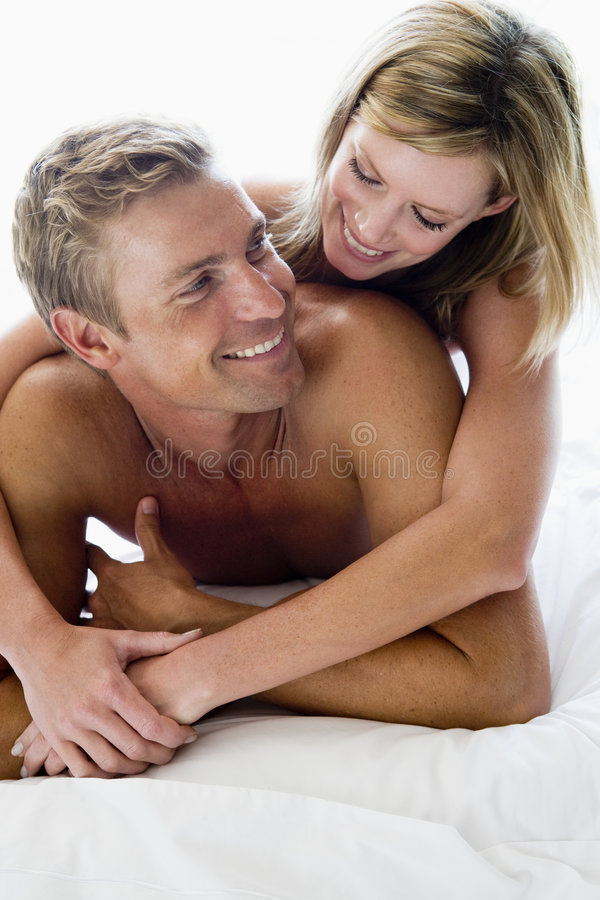 Paare, die beim Bettlächeln liegen lizenzfreies stockbild