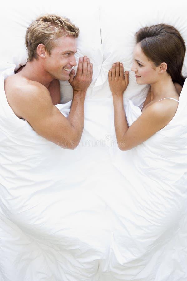 Paare, die beim Bettlächeln liegen stockfotografie