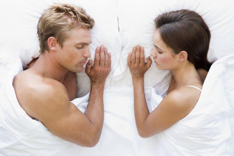 Paare, die beim Bettschlafen liegen lizenzfreie stockfotos
