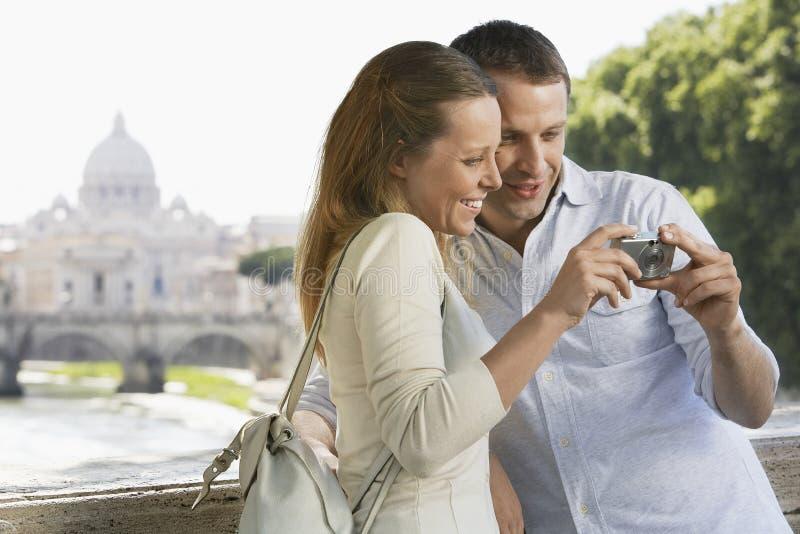 Paare, die Bilder auf Digitalkamera betrachten stockbilder