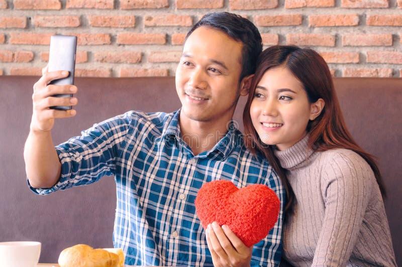Paare, die am Café sitzen und selfie nehmen stockfotografie