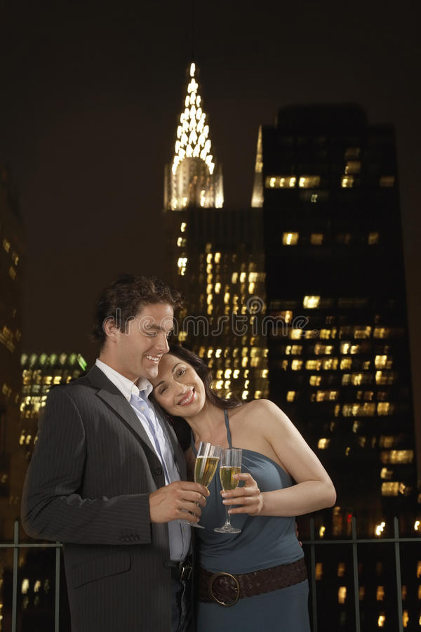 Paare, die Champagne Against New York Skyline rösten lizenzfreie stockfotos