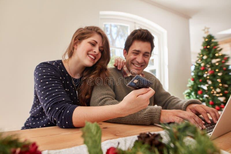 Paare, die das on-line-Einkaufen für Weihnachten tun lizenzfreies stockbild