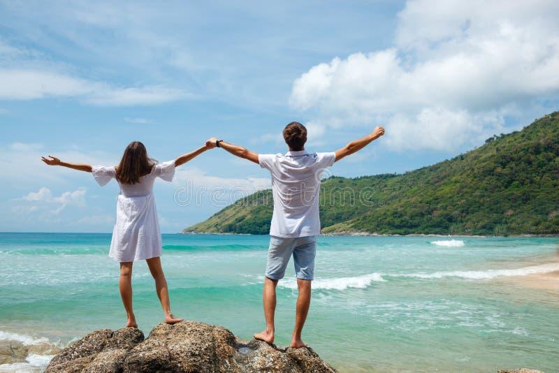 Paare, die in den Felsen über dem Meer stehen lizenzfreie stockfotos