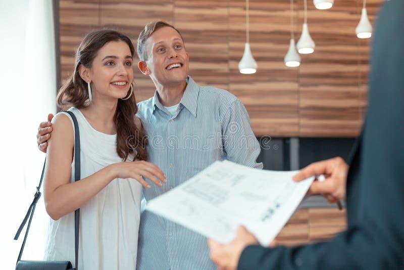 Paare, die den Grundstücksmakler gibt ihnen die Dokumente betrachten lizenzfreie stockbilder
