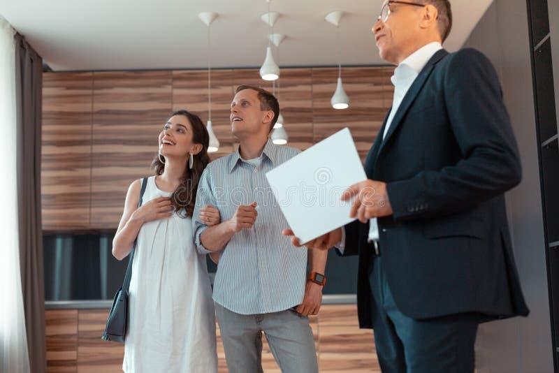 Paare, die den Raum bei der Stellung nahe Grundstücksmakler betrachten lizenzfreie stockfotos