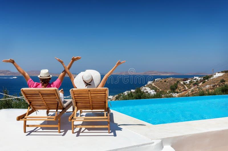 Paare, die in den Sonnenstühlen durch das Pool im Mittelmeer sitzen stockfoto