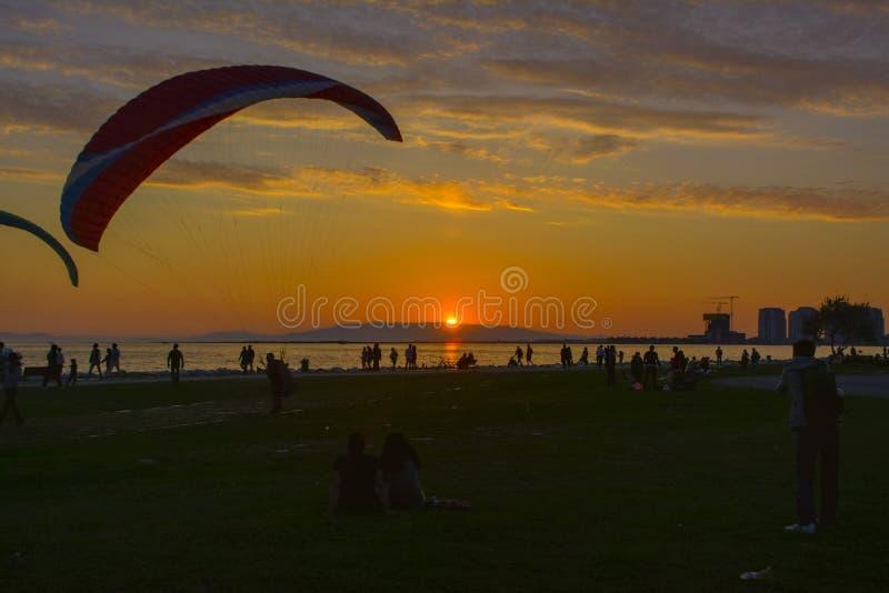 Paare, die den Sonnenuntergang auf dem Strand aufpassen stockbild