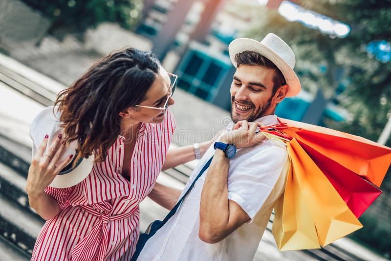 Paare, die den Spaß im Freien beim Handeln des Einkaufs haben lizenzfreies stockbild