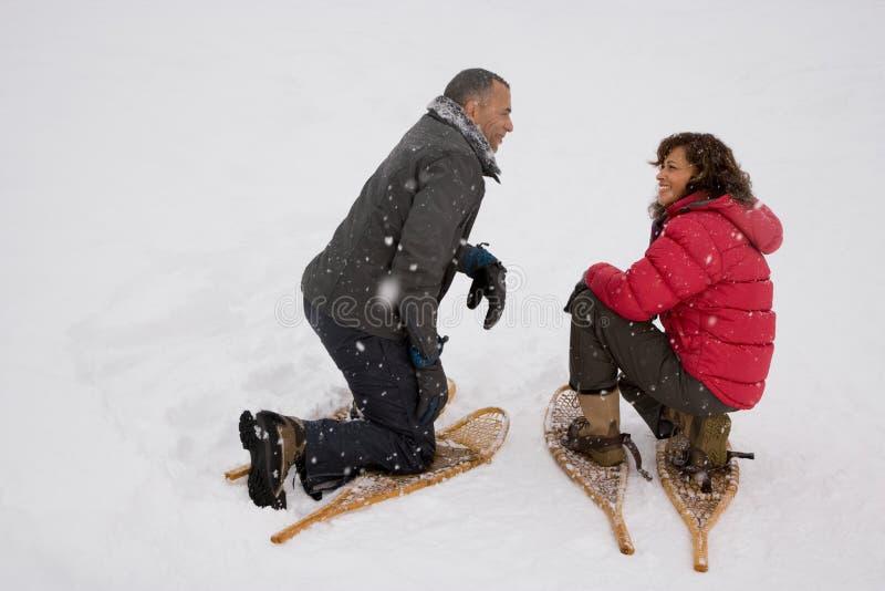 Paare, die in den tragenden Schneeschuhen des Schnees sich ducken stockfotografie