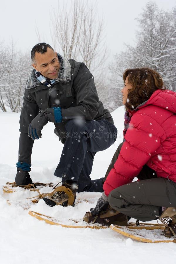 Paare, die in den tragenden Schneeschuhen des Schnees sich ducken stockfoto