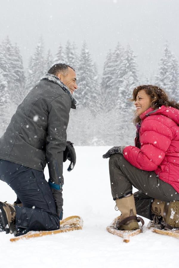 Paare, die in den tragenden Schneeschuhen des Schnees sich ducken lizenzfreies stockfoto