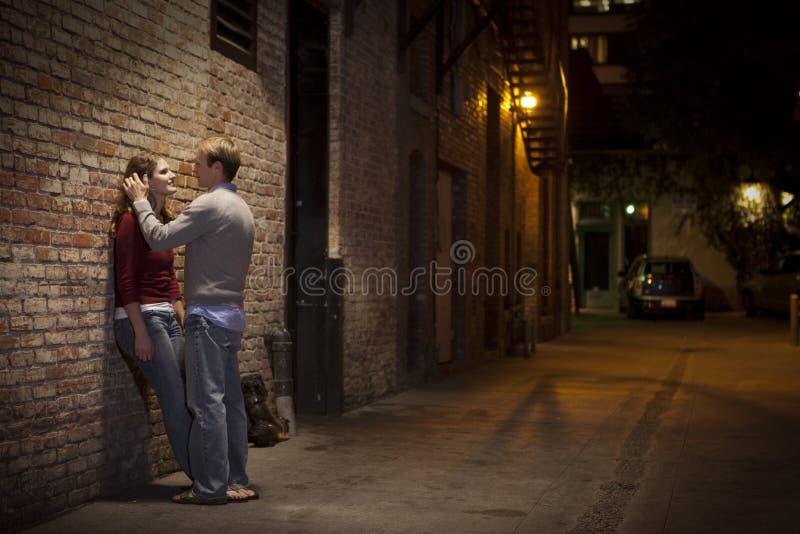 Paare, Die An Der Backsteinmauer Auf Gassenart Sich Lehnen Stockfoto