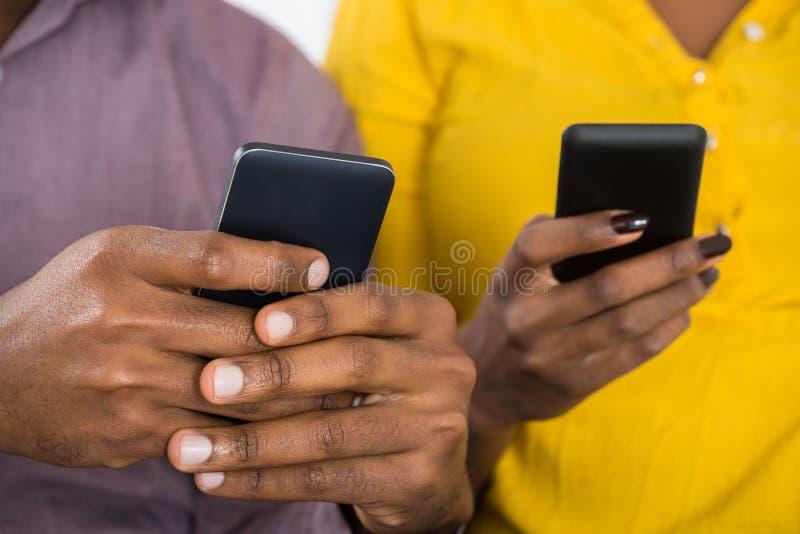 Paare, die in der Hand Handys halten lizenzfreies stockbild