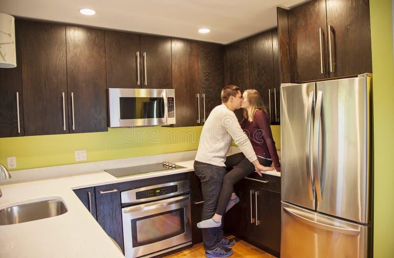 Paare, die in der Küche küssen lizenzfreie stockfotografie