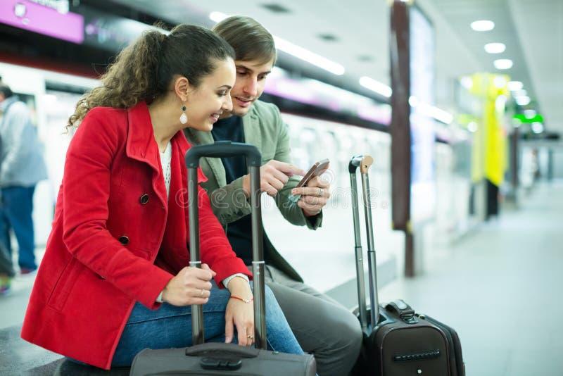 Paare, die an der Plattform sitzen lizenzfreie stockbilder