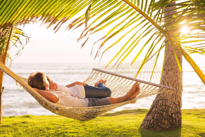 Paare, die in der tropischen Hängematte sich entspannen stockfotos