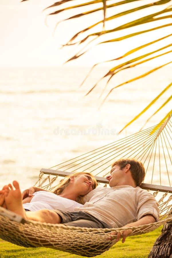 Paare, die in der tropischen Hängematte sich entspannen lizenzfreie stockfotos