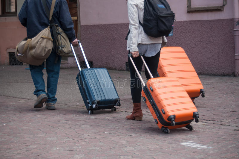 Paare, die in die Straße mit Koffer gehen lizenzfreie stockfotografie