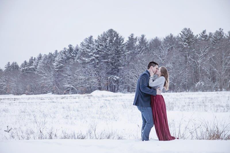Paare, die draußen im Winterschnee küssen stockfotografie