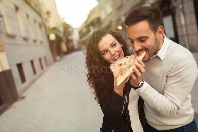 Paare, die draußen Pizza essen lizenzfreie stockbilder