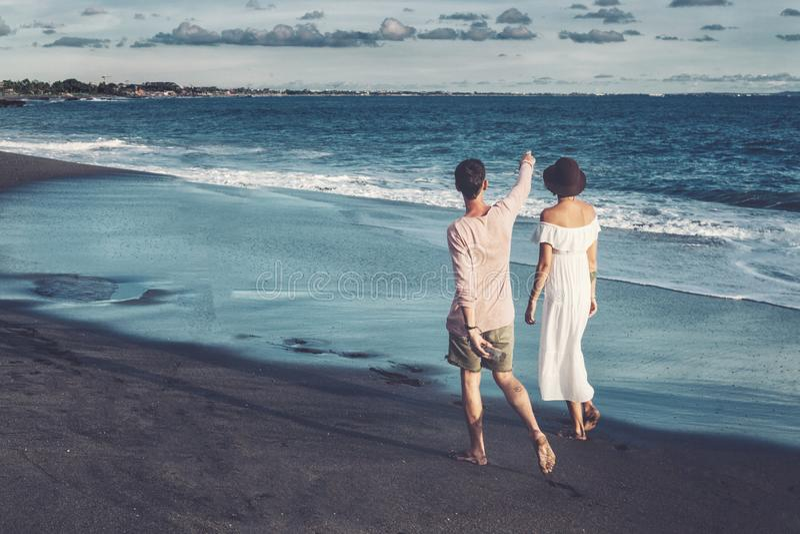 Paare, die durch Heron gehen Junges glückliches Paar, das auf dem lächelnden Halten des Strandes um einander geht stockfoto