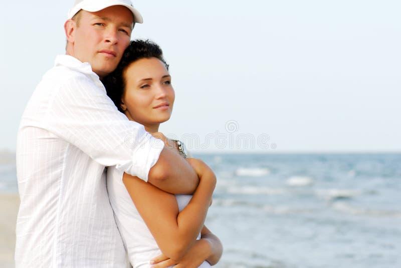 Paare, die durch Meer umfassen lizenzfreies stockfoto