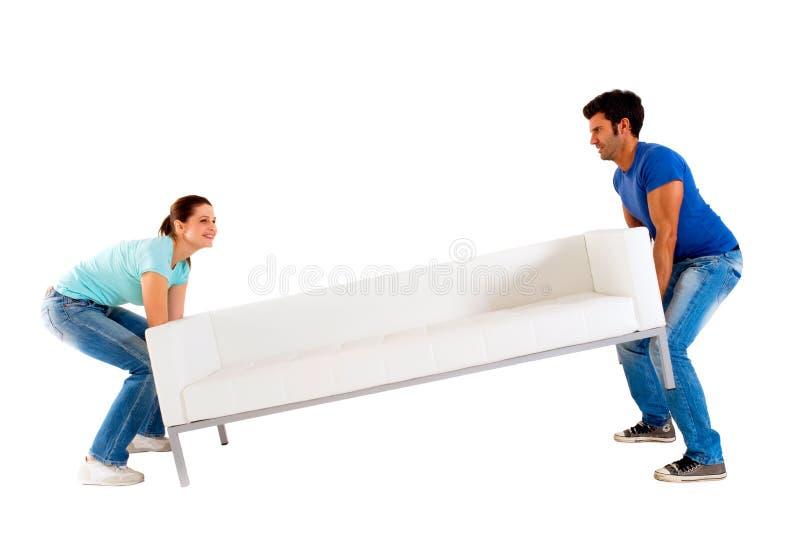 Paare, die ein Sofa tragen lizenzfreie stockfotografie