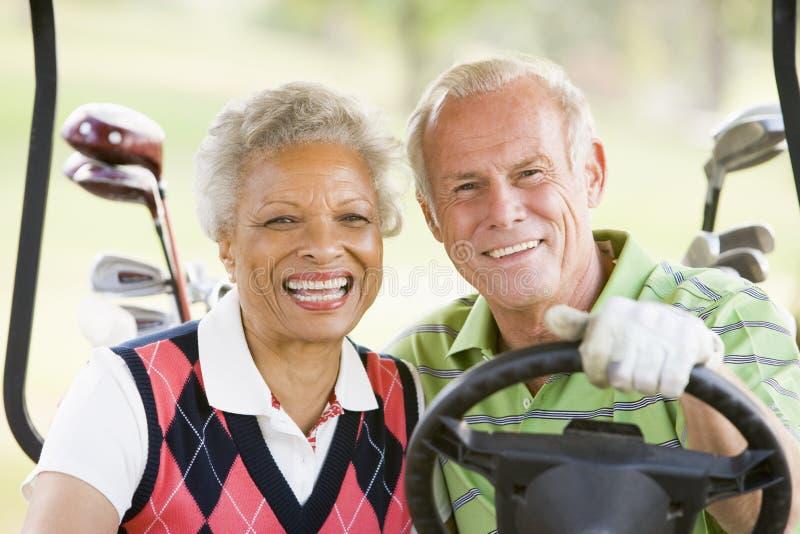 Paare, die ein Spiel des Golfs genießen lizenzfreies stockbild