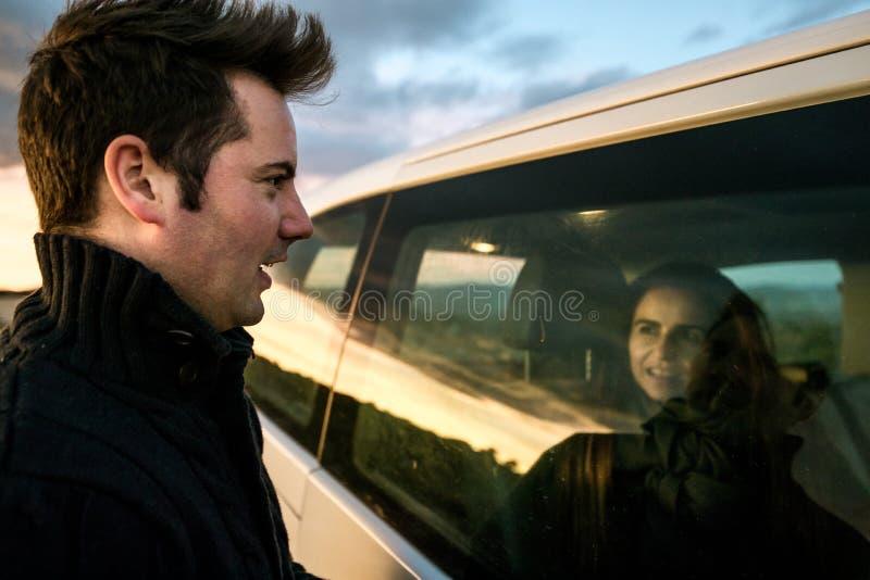Paare, die einander durch das Autofenster betrachten Freunde lächelnd und glücklich stockfotos