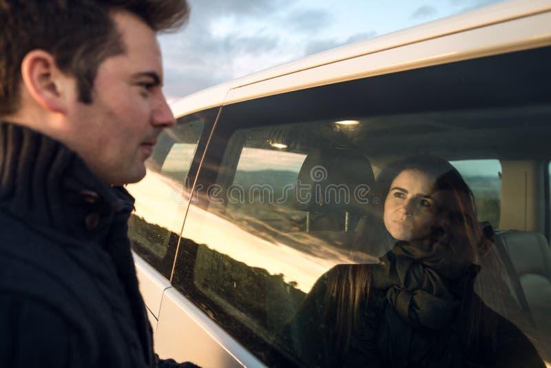 Paare, die einander durch das Autofenster betrachten Freunde lächelnd und glücklich stockfoto