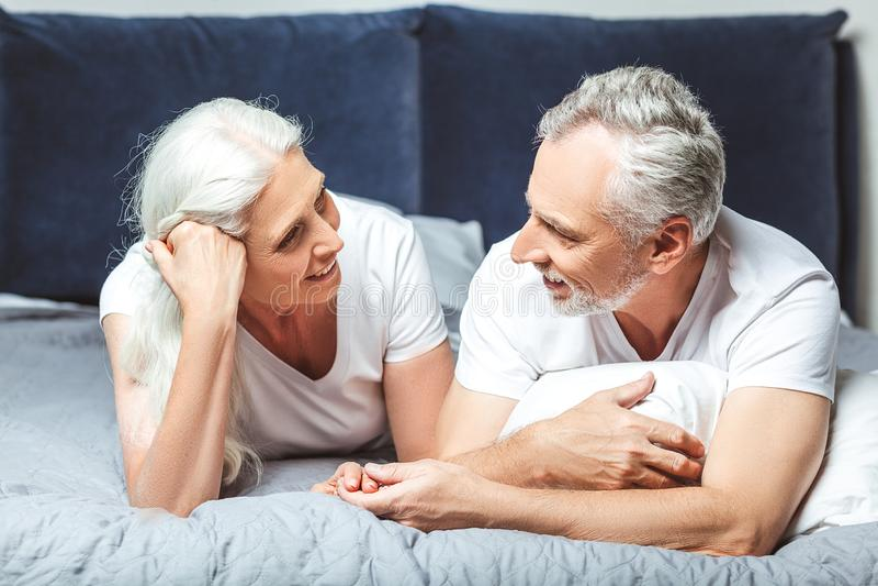 Paare, die einander liegend auf dem Bett betrachten lizenzfreies stockbild