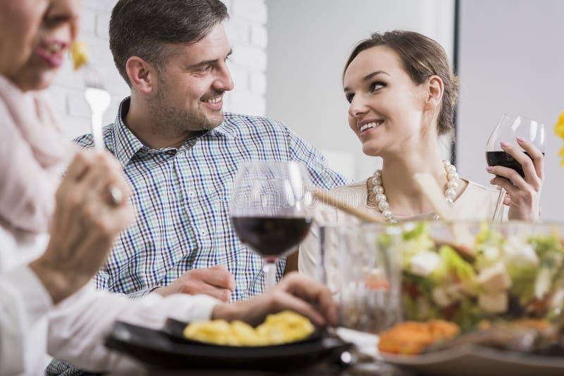 Paare, die an einem Tisch lächeln lizenzfreies stockbild