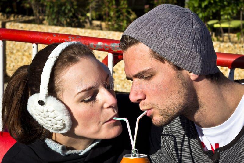 Paare, die einen Saft aus a-Dose heraus trinken stockbild