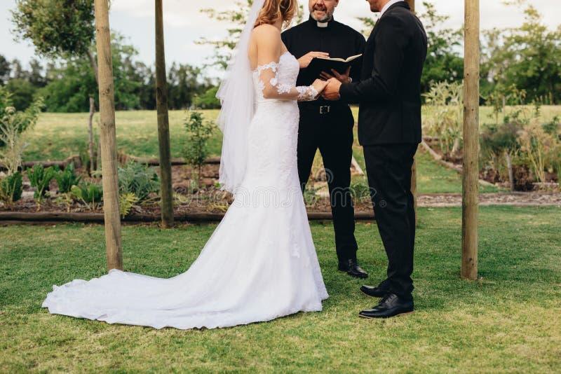 Paare, die an einer Hochzeits-Zeremonie im Freien heiraten lizenzfreie stockfotografie