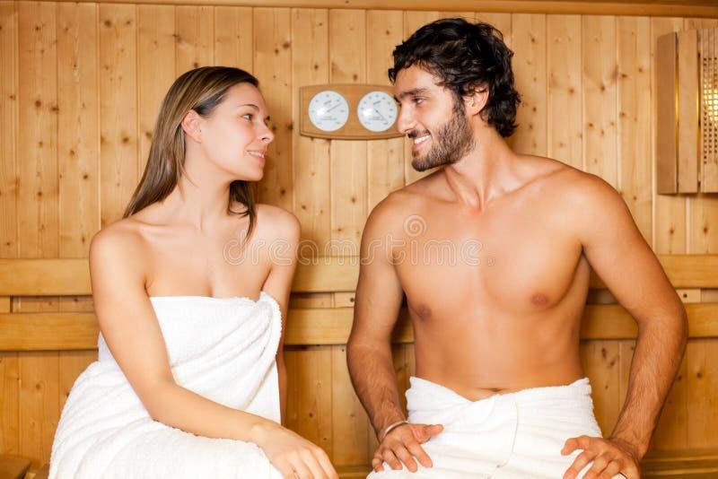Paare, die in einer Sauna sich entspannen stockbilder