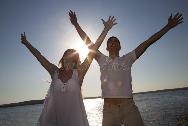 Paare, die für Freude auf dem Strand springen lizenzfreies stockbild